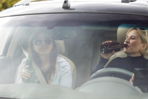 Two women drinking while driving a car